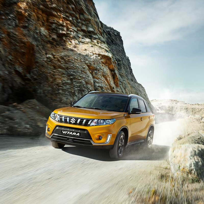 A yellow Vitara driving fast down a canyon road
