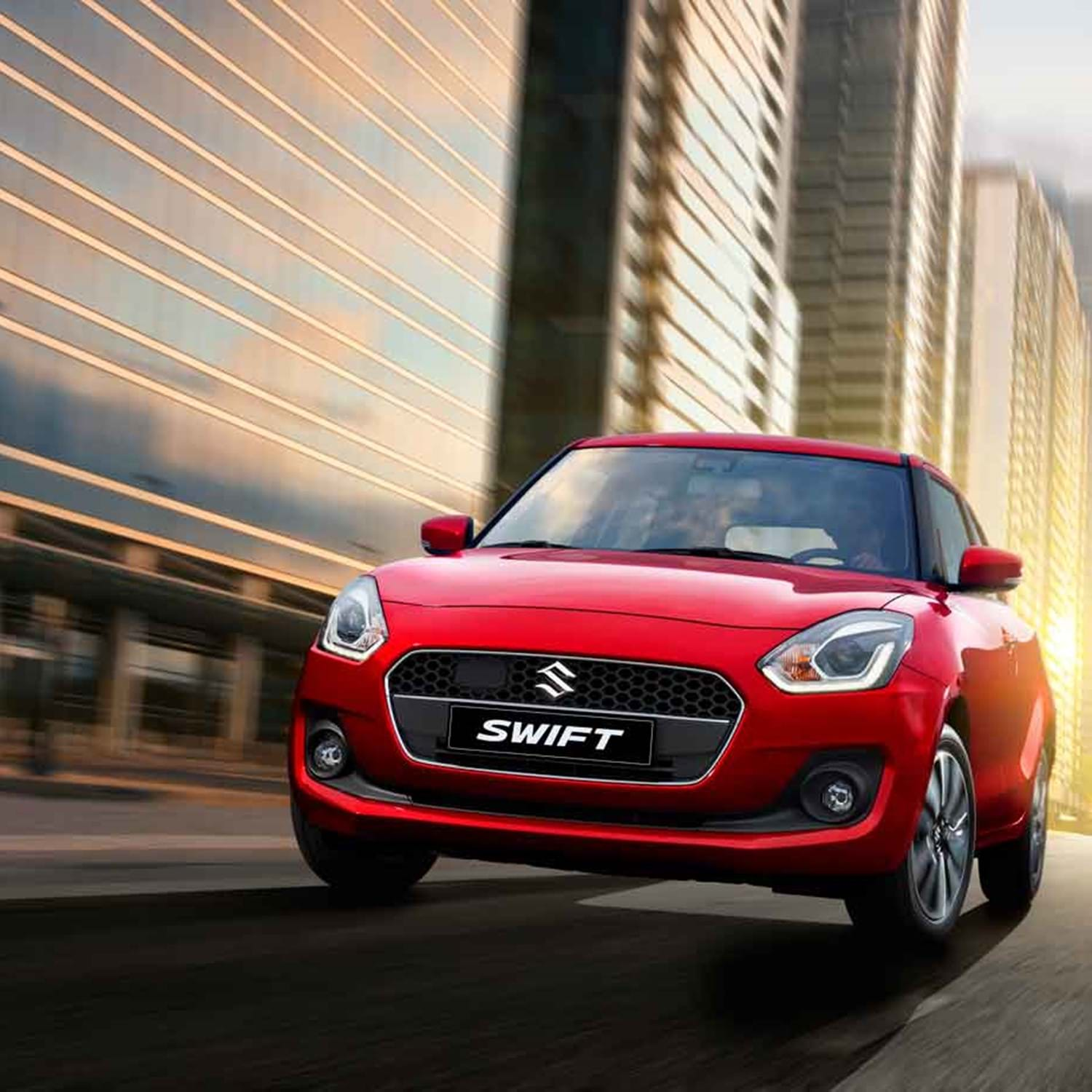 A red Swift driving through a city