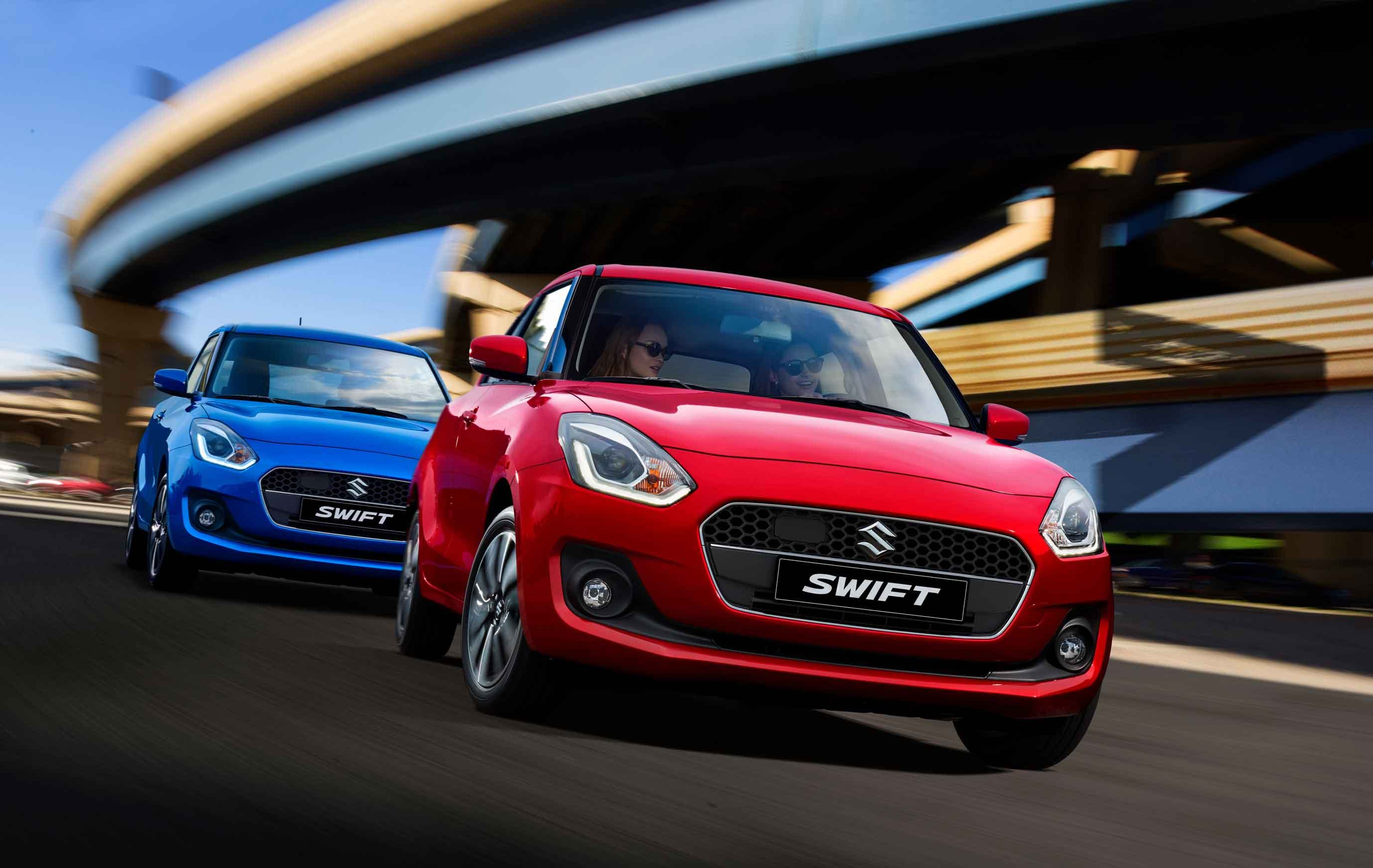 A red Suzuki Swift followed by a blue one