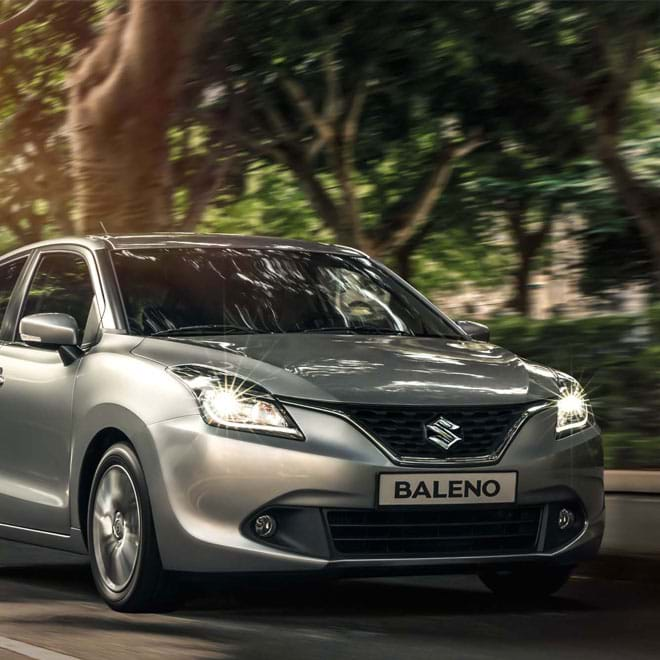 Suzuki Baleno driving through forest