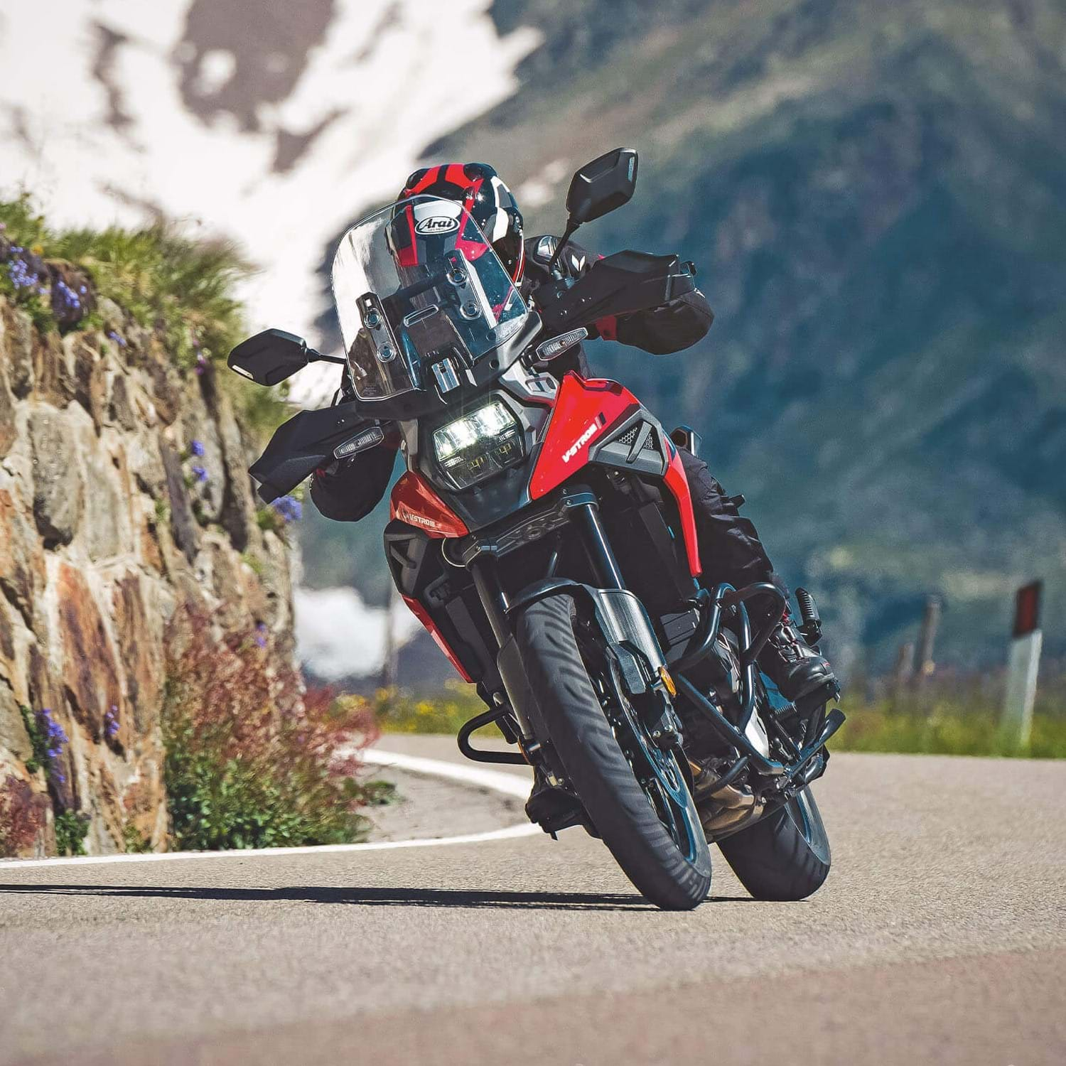 Suzuki V-Strom 1050XT Orange and White cornering on a mountain road. The Master of Adventure, the best all round adventure bike
