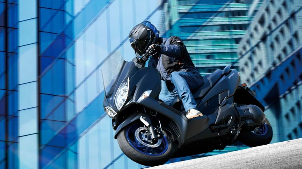 Suzuki Burgman 400 black. Rider on their way to work
