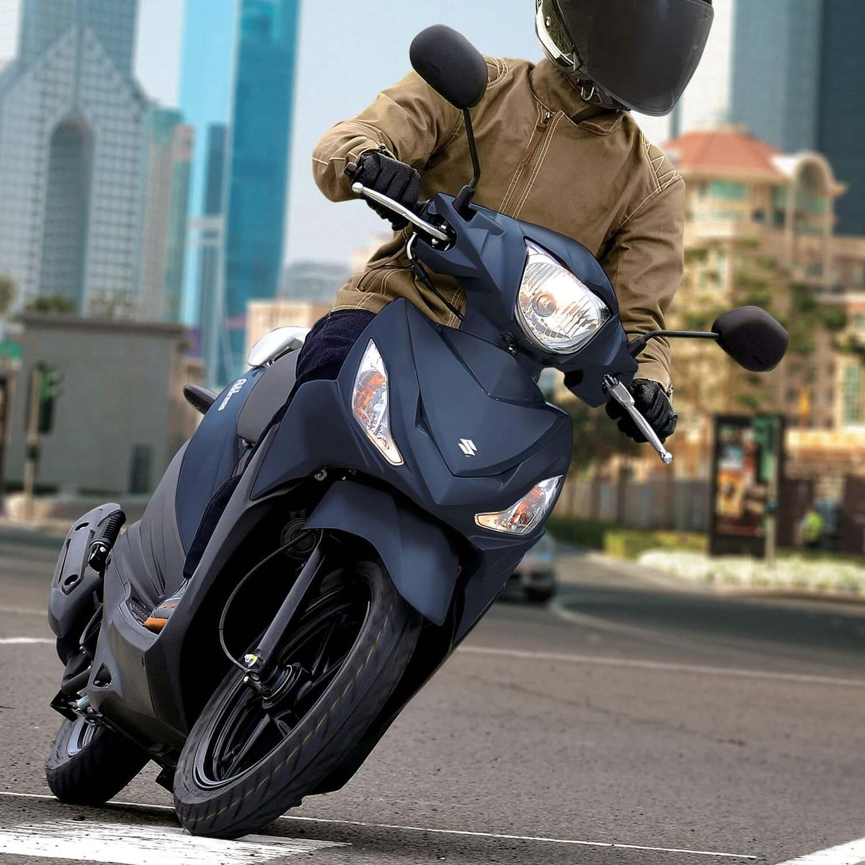 Suzuki Address scooter going around a corner with man going to work
