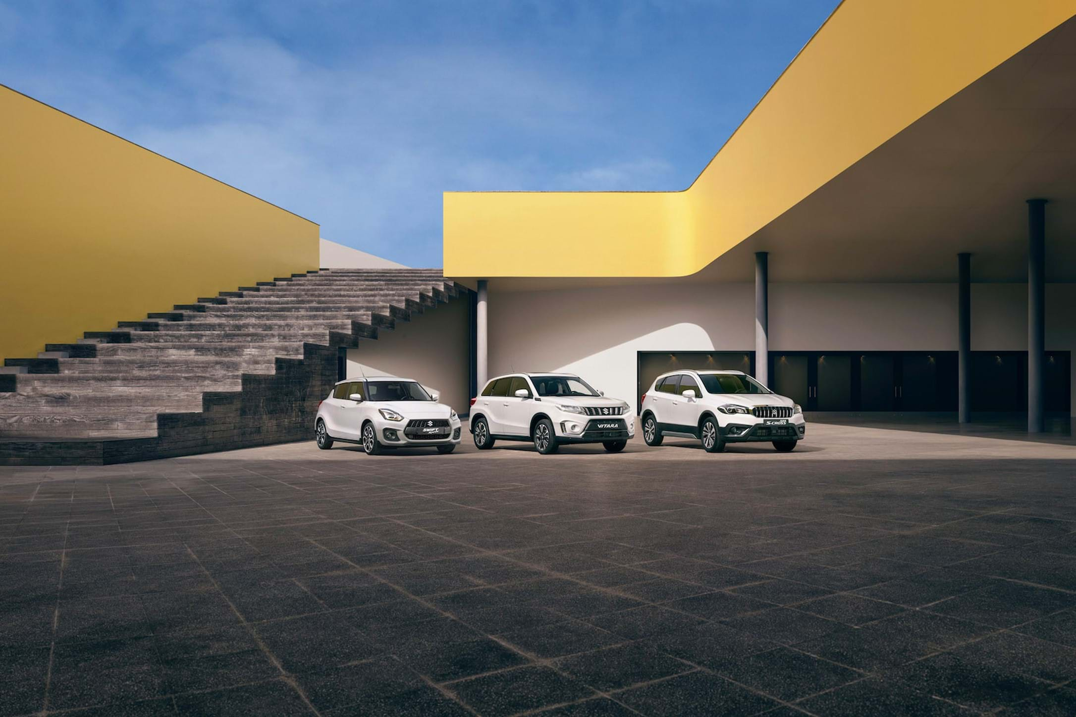 A Suzuki Swift sport, Vitara and S-Cross lined up in a courtyard
