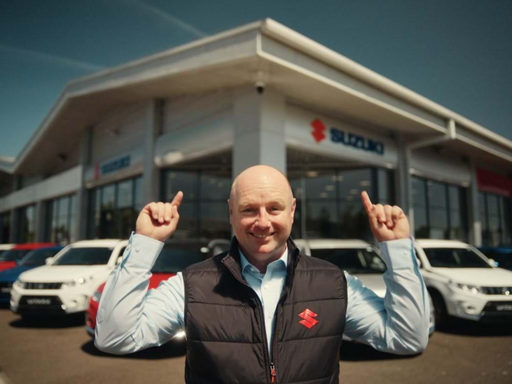 man standing in front of Suzuki dealership