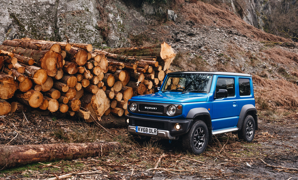Blue Jimny on rough terrain next to cut trees