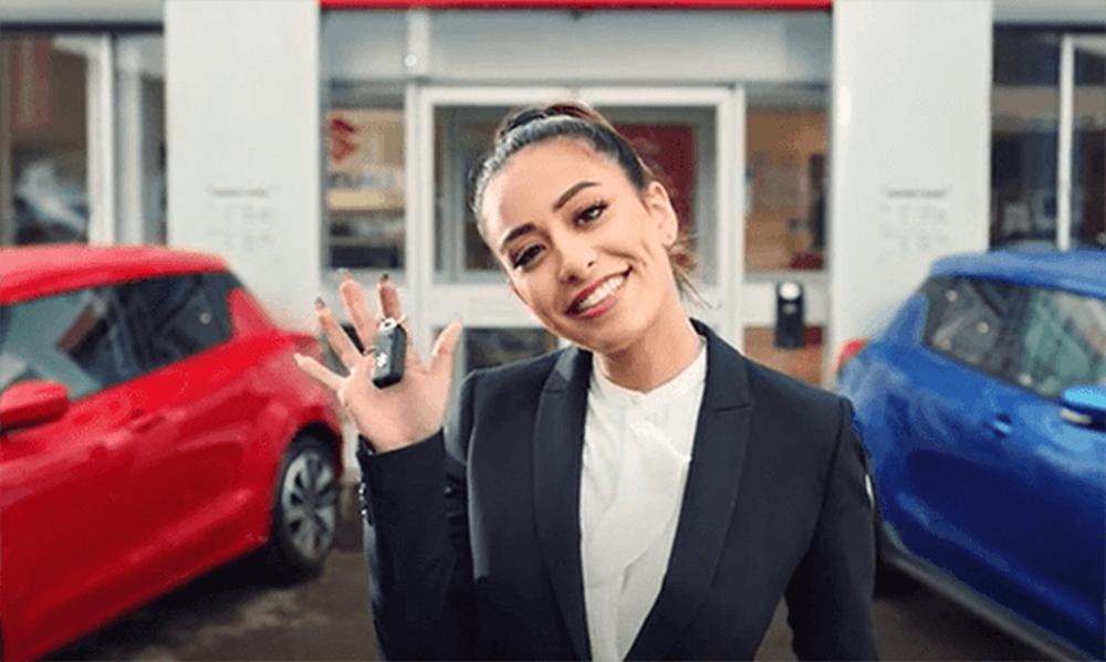 Dealer standing in front of Suzuki dealership