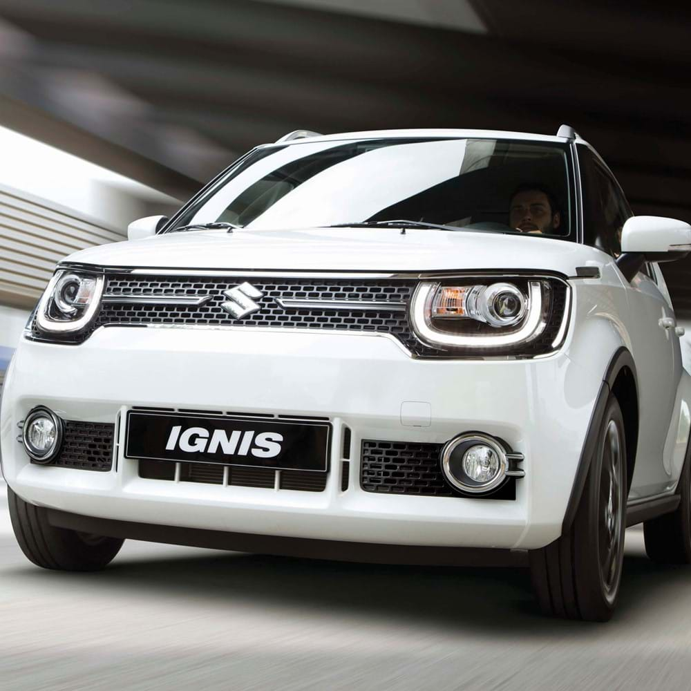 Side facing Suzuki Ignis driving under bridge